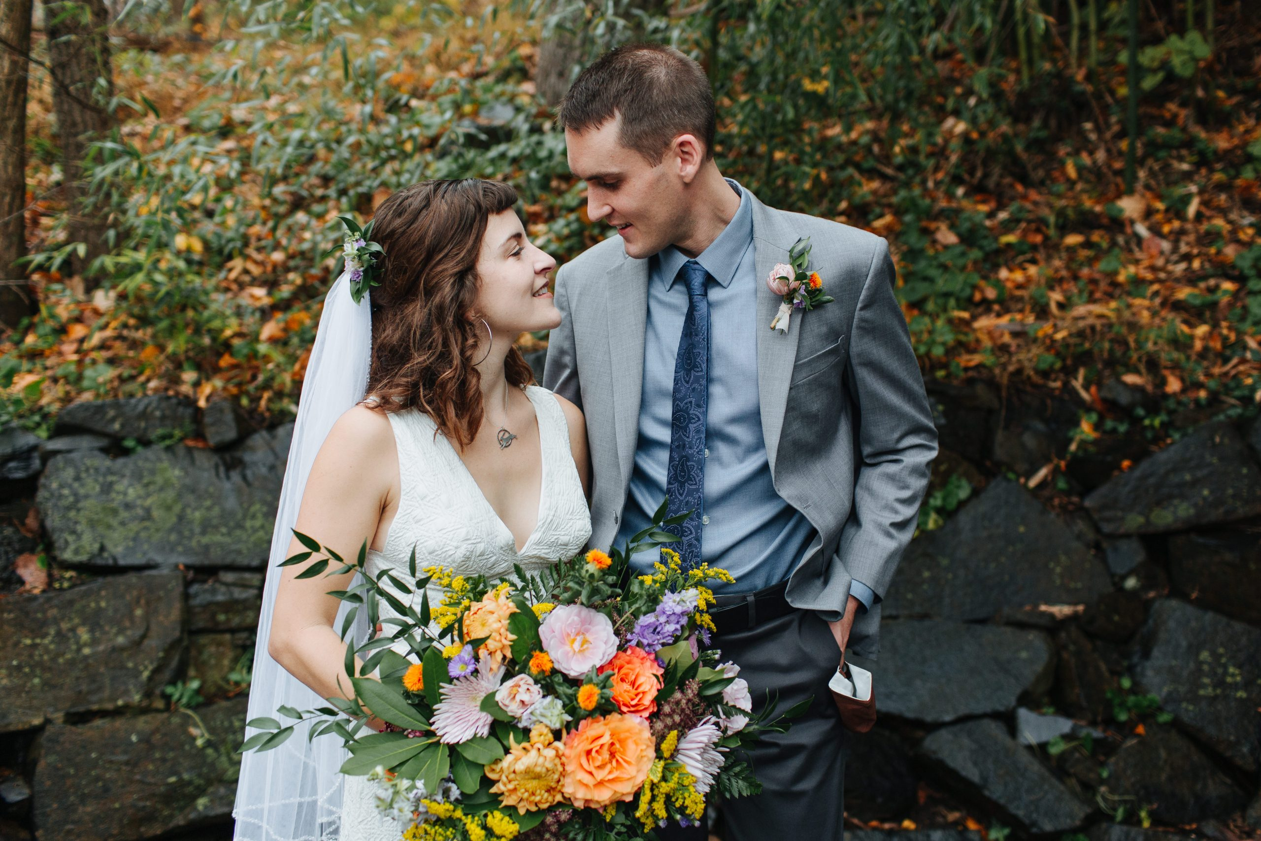 Caucasian couple looking at one another after self uniting in a micro wedding in Bucks County, PA. The bride has a white jumpsuit on, a short veil on her brown hair decorated with orange and purple flowers. The groom has on a grey suit coat and blue tie.